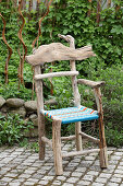 Rustic chair made from driftwood with seat made from colourful woven twine