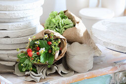 Bouquet of strawberry plants wrapped in paper in potter's workshop