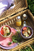 Pasta salad and small swing-top bottles in open picnic basket
