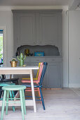 Table and brightly coloured chairs in front of grey dresser