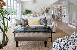 Leather ottoman, coffee table and couch with scatter cushions in open-plan interior with glass wall