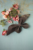 Leather bow, fabric flowers and ivy berries on grey surface