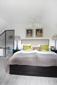 Double bed under chandelier in attic bedroom with ensuite bathroom in background