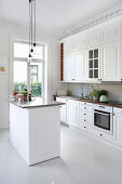 Island counter and stucco ceiling in white country-house kitchen