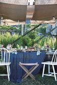 Fürs Sommerfest gedeckter Tisch unter Holzständern mit Stoffbahnen