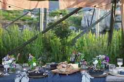 Fürs Sommerfest gedeckter Tisch unter Holzständern