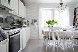 Dining table in vintage-style kitchen in white and grey