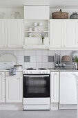 Old cooker in country-house kitchen decorated entirely in white