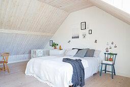 Simple attic bedroom with wood-clad walls
