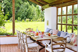 Set table on roofed terrace in summery garden