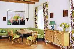 Green corner bench and rattan furniture in dining room with Oriental ambiance