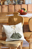 Cushion with appliqué doll motif on rustic wooden chair