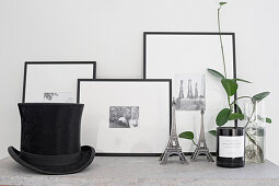 Houseplant, miniature Eiffel towers, framed black-and-white photos and opt hat on surface