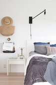 Grey bed linen and wall-mounted lamp in white bedroom