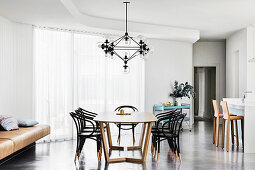 Dining area with designer table and Thonet chairs on concrete floor