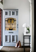 Open front door in the hallway with console table and white table lamp