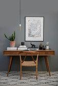 Stuhl und Schreibtisch aus Holz vor grauer Wand