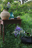 Raffia vase and blue glass jug on table next to basket of flowers in garden