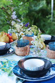 Table set in shades of blue with glasses in raffia holders in garden