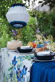 Table set in shades of blue below white and blue lanterns in garden