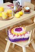Cushion with crocheted jersey cover on chair at breakfast table
