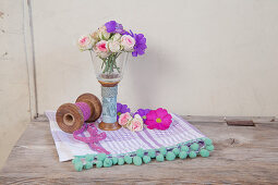 Flowers arranged in vase made from candle lantern and old yarn reel
