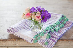 Primeln und Rosen im Glas auf einem Tuch mit Bommelborte