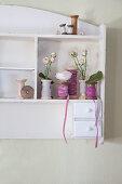 Garnrollen mit Stoffbändern und Blumen in einem Wandregal