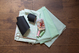 Chalkboard fabric and sewing utensils on mint-green patterned fabrics
