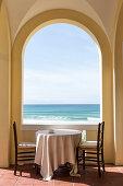 Tisch und zwei Stühle in der Loggia mit pittoreskem Meerpanorama