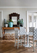 Chairs with polka-dot backrests at round dining table in front of wood-framed mirror and potted plants on console table