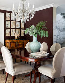 Antique table and elegant upholstered chairs below chandelier