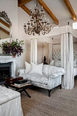 Four-poster bed and pale grey couch in elegant, classic bedroom