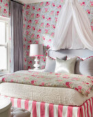 Rose-patterned wallpaper and bed with canopy in pretty bedroom