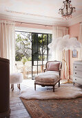 Antique, French day bed and floor lamp with ostrich feathers in front of a balcony door