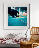Designer lamp on marble shelf, photo art above, rattan chair in foreground