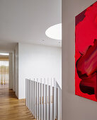 Large-sized artwork in shades of red on a white wall in the hallway