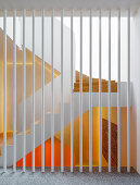 White painted metal bars as a room divider, view of the stairwell