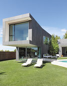 Clipped lawn surrounding architect-designed house with swimming pool