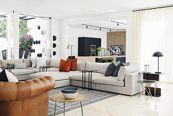 Grey sofa set in open-plan living area with travertine flags on floor