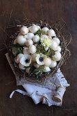 weiße Zwiebeln, Anemonen und Efeubeeren in einem Kranz