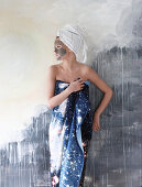 Woman wrapped in towel and turban with face mask leaning against mural