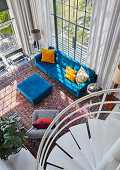 Blick auf blaue Polstermöbel in offenem Wohnraum mit doppelter Raumhöhe
