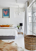 Double bed, cowhide rug and basket in white bedroom