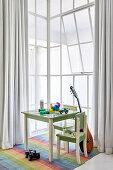 Kindertisch mit Spielzeugen, Stühle und Gitarre vor Fenster in hohem Raum