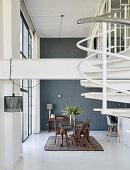 Esstisch mit Stühlen vor Fensterfront in hohem Raum, im Vordergrund weiße Wendeltreppe