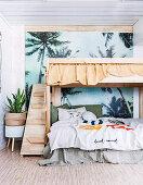 Etagenbett aus Holz vor Palmentapete im Kinderzimmer