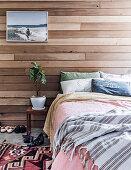 Doppelbett und Nachttisch mit Zimmerpflanze vor Wandverkleidung aus recyceltem Zedernholz