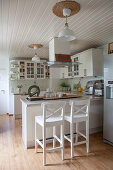 Breakfast bar and bar stools in white kitchen