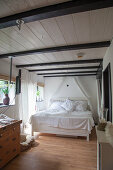 White bed with white bed linen in converted barn